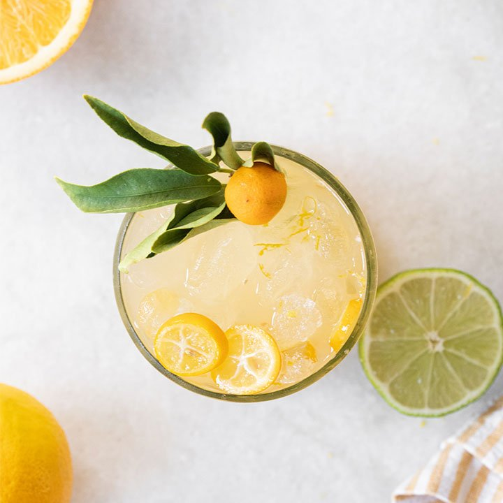 mixed drink with citrus garnish in kitchen setting