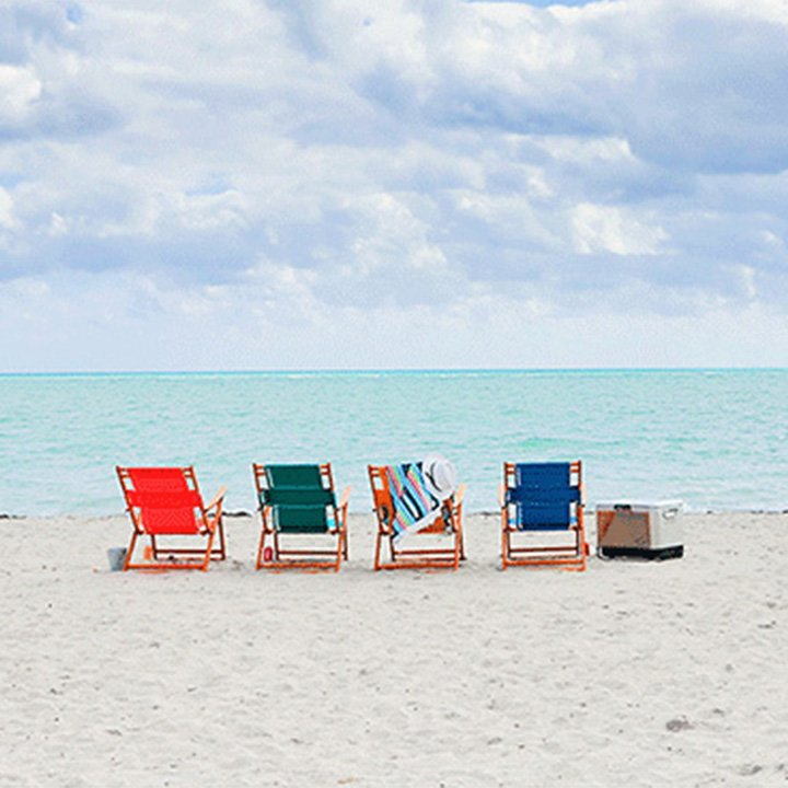 4 chairs on the beach facing the ocean